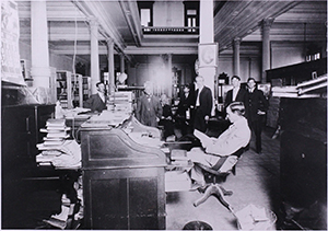 Image of the State Library circa 1910 showing roll-top desk and early electrical wiring.